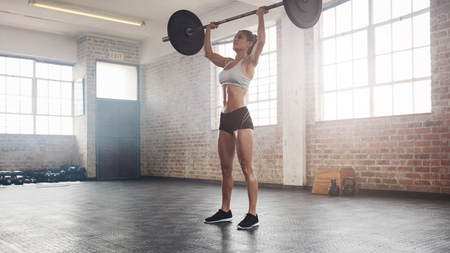 Full length image of strong young woman exercising with barbell. Fit female athlete lifting heavy weights.