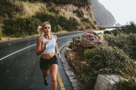 Fitness woman running on highway around the mountains. Female athlete training outdoors during rain.の写真素材