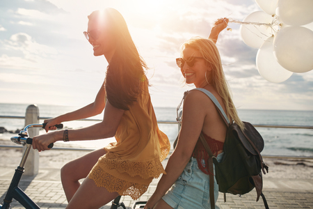 Happy young women riding a bicycle together with balloons. Best friends having fun on a cycle by the sea.