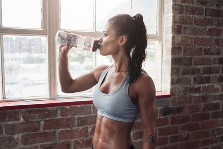 Foto de Fit young woman drinking water in the gym. Muscular woman taking break after exercise. - Imagen libre de derechos
