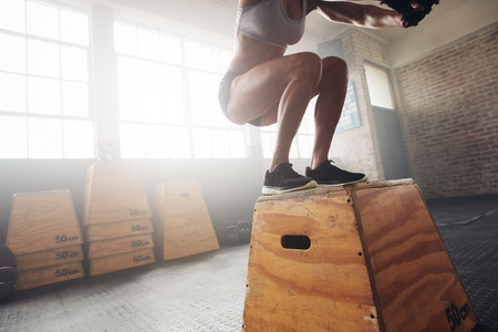 Photo for Fit young woman box jumping at a crossfit gym. Female athlete is performing box jumps at gym, with focus on legs. - Royalty Free Image