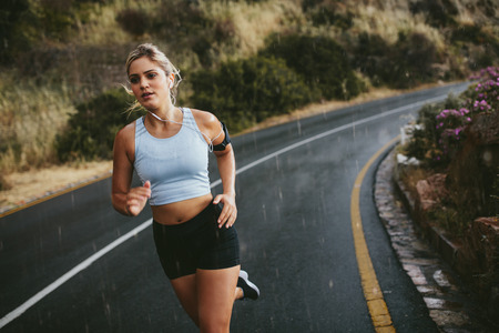 Fit young woman jogging outdoors on highway. Female athlete training running on a rainy day.の写真素材
