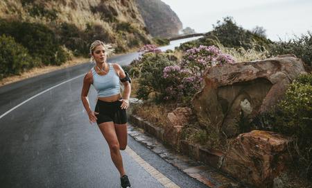 Foto de Fitness woman running on the road around mountains under rain. Female athlete training outdoors. - Imagen libre de derechos