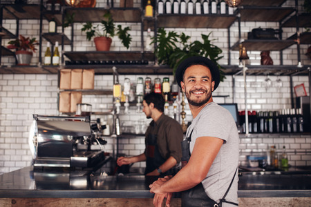 Coffee shop owner standing with barista working behind the counter making drinks.