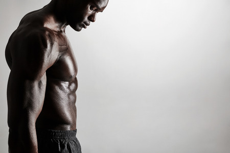 Foto de Close-up of shirtless african man standing against grey background. Cropped image of torso of a muscular man with copyspace. - Imagen libre de derechos