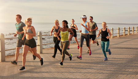 Photo pour Group of runners running on urban street by the seaside. Healthy young people training together outdoors. - image libre de droit