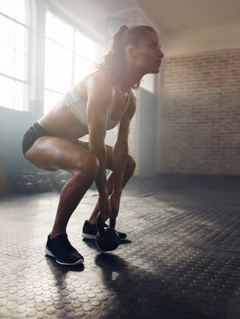 Fitness woman working out with kettle bell. Female model with muscular body exercise with kettlebell at cross fit gym.