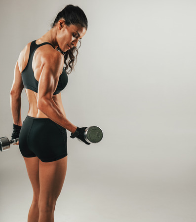 Single sweating female athlete lifting chrome dumbbell over gray background with copy space