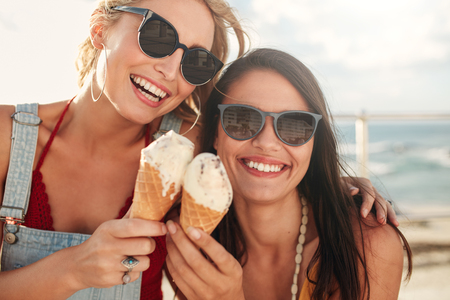 Shot of two young friends enjoying ice cream together on a summer day outdoors. Close up of cheerful female buddies eating icecream.