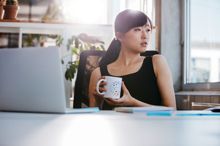 Foto de Portrait of relaxed young woman sitting at her desk holding cup of coffee and looking away. Asian business woman taking coffee break in office. - Imagen libre de derechos