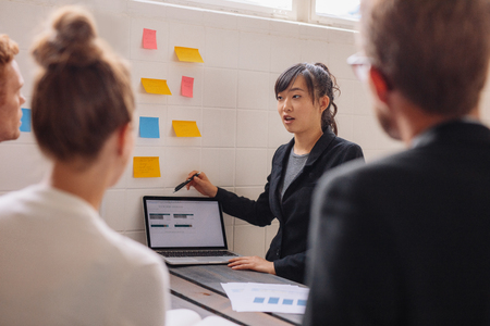 Foto de Asian businesswoman explaining her new business ideas to colleagues with laptop and adhesive notes on wall. Young female executive giving presentation to coworkers. - Imagen libre de derechos