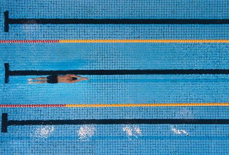 Top view shot of young man swimming laps in a swimming pool. Male swimmer gliding through the water.