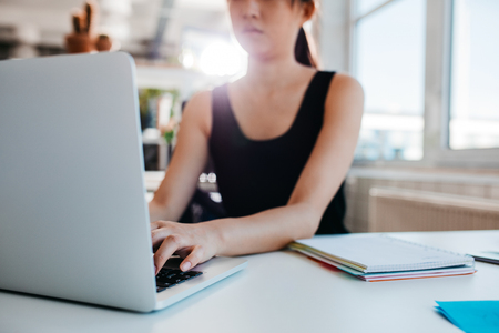 Cropped shot of woman working on laptop at office. Focus on hands of female typing on laptop keyboard.