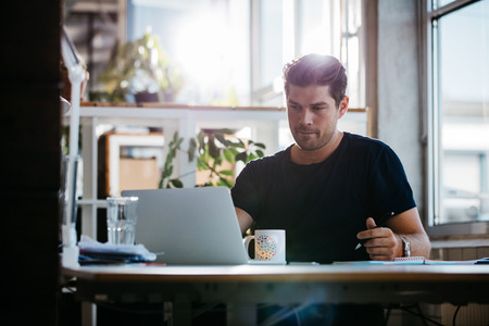 Photo for Shot of handsome young man sitting at his desk looking at laptop and writing notes. Businessman working in his office. - Royalty Free Image