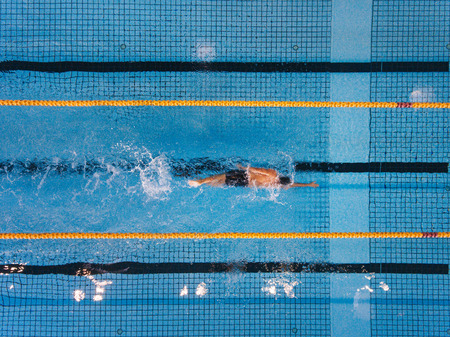 Top view shot of young man swimming laps in a swimming pool. Male swimmer swimming the front crawl in a pool.