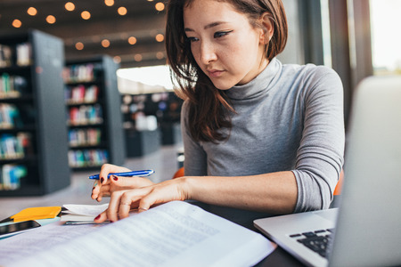 Photo pour Young woman studying on a book and taking down note while sitting at the library desk. Asian female student preparing for final exams. - image libre de droit