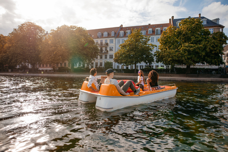 Photo pour Shot of teenage friends relaxing on pedal boat in lake. Young men and women boating and enjoying holidays. - image libre de droit