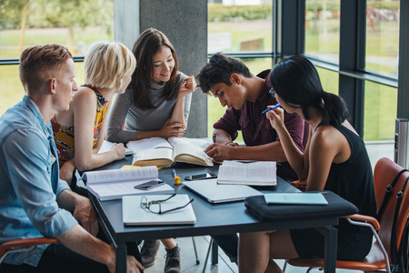 Foto de Young people sitting at table working on school assignment. Multiracial group of students studying together in a library. - Imagen libre de derechos