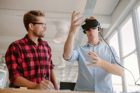 Shot of two young men testing virtual reality headset. Business men discussing and testing VR glasses.