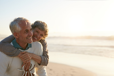 Portrait of happy mature man being embraced by his wife at the beach. Senior couple having fun at the sea shore.の写真素材