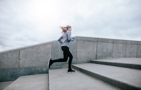 Photo pour Side view full length shot of fit young woman running up stairs. Fitness female on morning workout. - image libre de droit