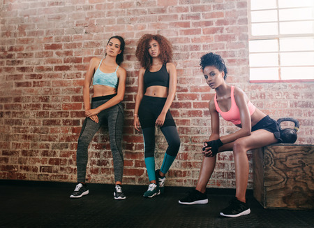 Foto de Portrait of young women resting after workout in gym. Mixed race group of female relaxing in gym after training. - Imagen libre de derechos