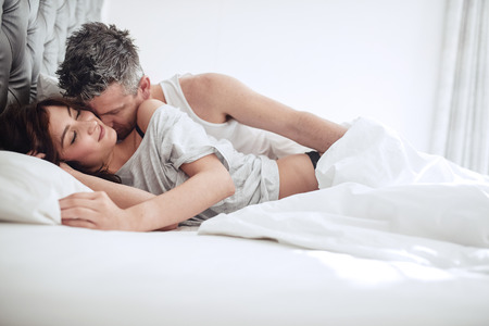 Photo pour Intimate young couple enjoying sensual foreplay on bed. Man kissing on neck of woman. - image libre de droit
