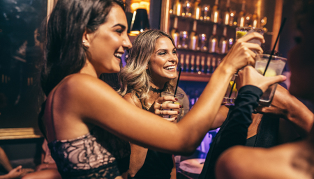 Photo for Group of young people celebrating at pub. Friends toasting cocktails in night club. - Royalty Free Image