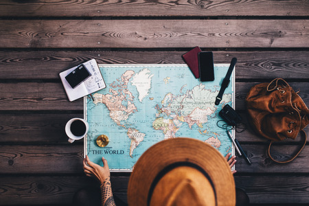 Photo pour Young woman planning vacation using world map and compass along with other travel accessories. Tourist wearing brown hat looking at the world map. - image libre de droit