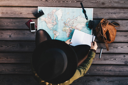 Photo pour Top view of woman wearing hat making tour plan using a world map. Tourist exploring the world map with travel accessories around. - image libre de droit
