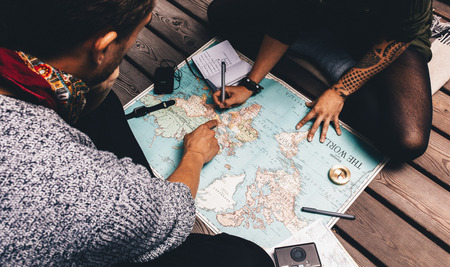 Photo pour Couple planning vacation using a world map. Man pointing at the map while the woman is making notes in diary. - image libre de droit