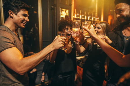 Photo pour Group of men and women enjoying drinks at nightclub. Young people at bar toasting cocktails and laughing. - image libre de droit