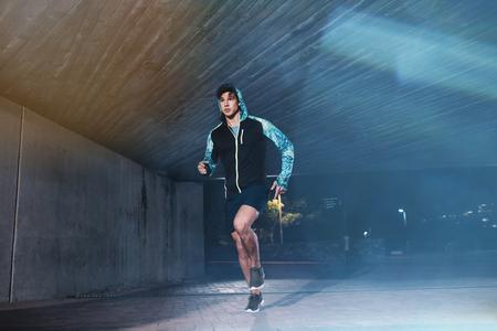 Foto de Full length shot of young athlete running under bridge in city. Fit young man jogging in the city. - Imagen libre de derechos