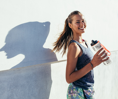 Foto de Shot of beautiful female runner standing outdoors holding water bottle. Fitness woman taking a break after running workout. - Imagen libre de derechos