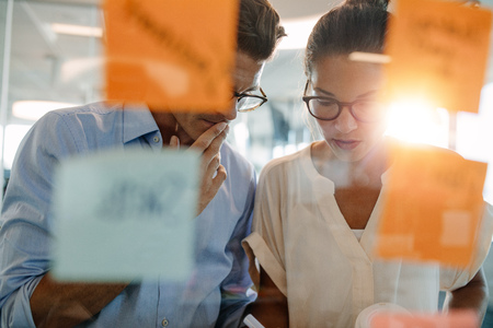 Two business professionals standing behind the glass wall with sticky notes and discussing. Colleagues brainstorming on new business ideas in office.