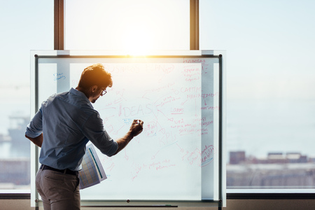 Photo pour Businessman making a presentation at office. Entrepreneur using whiteboard to present ideas for business planning and decision making. - image libre de droit