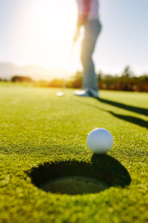 Foto de Golf ball at the edge of hole with player in background. Professional golfer putting ball into the hole on a sunny day. - Imagen libre de derechos