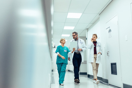 Photo pour Group of medics with clipboard discussing along hospital corridor. Doctor and nurse briefing medical report with female colleague talking on mobile phone. - image libre de droit