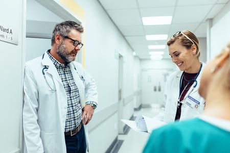Foto de Doctor with colleagues standing in hospital hallway. Hospital staff working and looking at medical reports. - Imagen libre de derechos