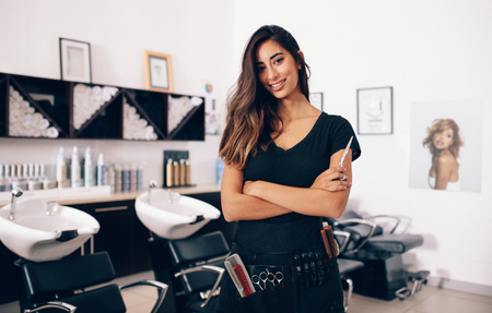 Female hairdresser in salon holding scissors in hand. Smiling young hairdresser standing in salon.