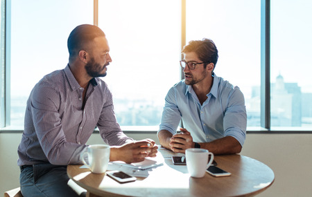 Photo for Business executives discussing work in office. Two businessmen sitting on a round table and discussing business matters. - Royalty Free Image