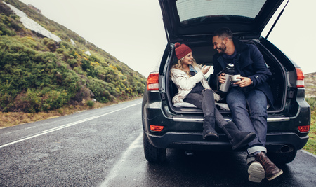 Photo pour Happy young couple having a coffee break during road trip in countryside. Man and woman sitting in car trunk and having coffee. - image libre de droit
