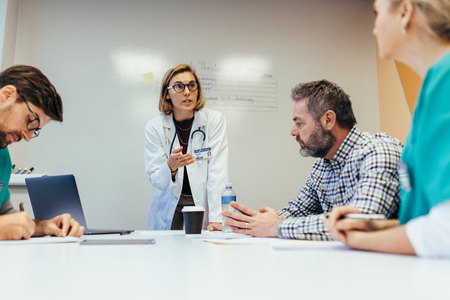 Photo pour Woman empowerment. Female doctor leading a meeting with her staff in boardroom. Woman medical professional briefing her colleagues. - image libre de droit
