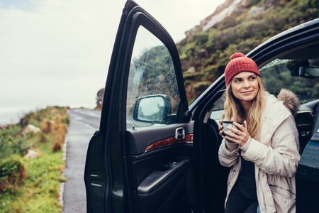 Beautiful female standing by the car with coffee. Smiling woman holding coffee and looking away.