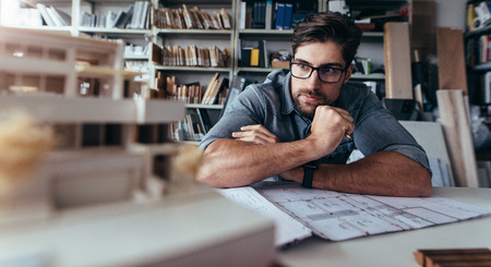 Architect looking at house model and thinking. Creative designer sitting in office and working on new project.