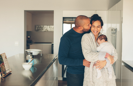 Photo pour Man kissing his wife holding a newborn baby boy in kitchen. Lovely young family of three in morning in kitchen. - image libre de droit