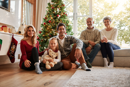 Photo pour Portrait of multi generation family in front of christmas tree. Happy family sitting at home during christmas. - image libre de droit