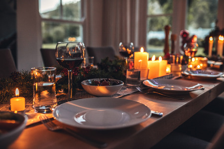 Photo pour Close up shot of christmas festive table with no people. Dining table with plates, wine glasses and candles. - image libre de droit