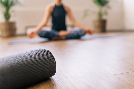 Foto de Close up of rolled yoga mat in fitness center and blurred woman at the back in lotus yoga pose. Fitness mat on floor with woman practising yoga in background. - Imagen libre de derechos