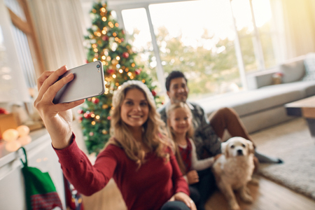 Happy family making selfie on smartphone. They are sitting near Christmas tree with a dog. Woman with family taking self portrait using smartphone during Christmas at home. Focus on mobile phone and female hand.